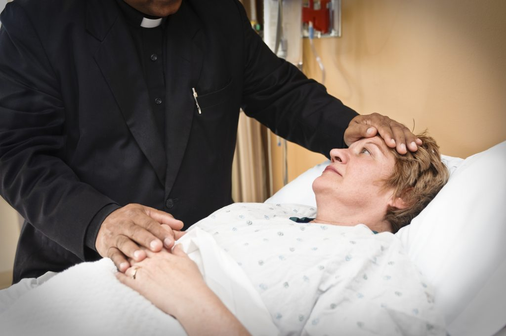 Priest seeing a patient in a hospital