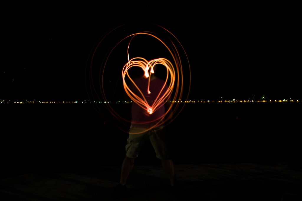 A photo of a man painting heart with light flash